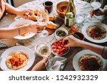 friends having a pasta dinner... | Shutterstock . vector #1242932329