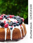 Fresh mixed berries vanilla bundt cake with icing in a garden - stock photo
