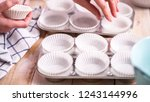 lining metal muffin pan with... | Shutterstock . vector #1243144996