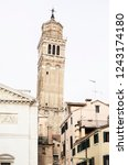 Small photo of Tower askew a church with houses in Venice in Italy
