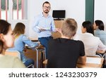 positive male teacher is giving ... | Shutterstock . vector #1243230379