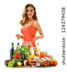 Young woman with variety of grocery products including vegetables, fruits, meat, dairy and wine - stock photo