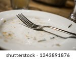 fork on a plate after a meal.... | Shutterstock . vector #1243891876