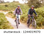 senior couple riding mountain... | Shutterstock . vector #1244019070