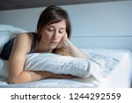 sad woman can't sleep lying in... | Shutterstock . vector #1244292559