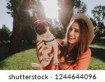 Stock photo waist up portrait of cheerful woman in hat is walking in green park and hugging her nice dog 1244644096