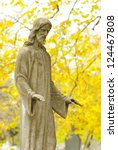 Jesus Christ sculpture in a cemetery at fall - stock photo