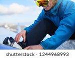 snowboarder straps in his legs... | Shutterstock . vector #1244968993