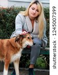 Stock photo beautiful girl with his shetland sheepdog dog sitting and posing in front of camera on wooden bench 1245007399
