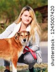 Stock photo pretty girl with his shetland sheepdog dog at nature park outdoor is standing and posing in front 1245007420