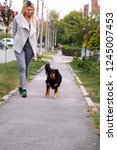 Stock photo woman walking with his female small mixed breed dog on leash posing in front of camera portrait 1245007453