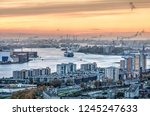 Small photo of Rotterdam, The Netherlands, November 12, 2018: aerial view of the Nieuwe Maas river meandering between industrial areas and city neighbourhoods towards the Northsea under a red sky