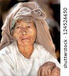 YANGOON, MYANMAR - NOVEMBER 9 ; An unidentified older woman is posing on Nov.9 2011, Yangoon, Myanmar. The life expectancy of woman in myanmar is 64 years . - stock photo