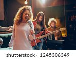 Small photo of Jazz band preparing for the gig. In foreground woman singing while the rest of the band playing bass guitar, clavier and acoustic guitar. Home music studio interior.