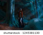 Small photo of Red-haired attractive slender girl in a long dark blue dress, cloak with a hood and open chest and leather boots standing in a dark forest in the rays of moonlight. the young princess has gone astray