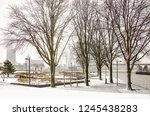 Small photo of Rotterdam, The Netherlands, December 11, 2017: light snow falling on the little park at Leuvehoofd by the river Nieuwe Maas, with Erasmus bridge and the soutbank riverfront inthe background
