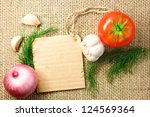 tomato, onion and garlic with cardboard price tag on sacking background - stock photo