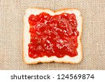 slice of bread with strawberry jam on sacking background - stock photo