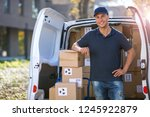smiling delivery man standing... | Shutterstock . vector #1245922879