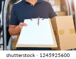 courier with clipboard and... | Shutterstock . vector #1245925600