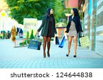 happy girls shopping on crowded city street - stock photo