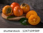 ripe persimmon fruits in a cork ... | Shutterstock . vector #1247109589