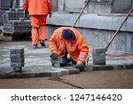 worker putting down paving slub ... | Shutterstock . vector #1247146420
