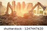 backhoe with raised bucket at... | Shutterstock . vector #1247447620