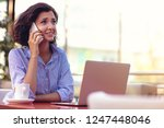 businesswoman using phone while ... | Shutterstock . vector #1247448046