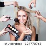 Many Hands Applying Make Up On...