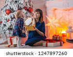 child with mom with gifts near... | Shutterstock . vector #1247897260