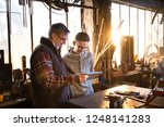 a craftsman and his young... | Shutterstock . vector #1248141283