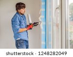 man in a blue shirt does window ... | Shutterstock . vector #1248282049