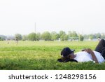 man napping in a field in... | Shutterstock . vector #1248298156
