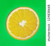 Slice of orange on green drop background - stock photo