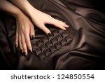 Closeup of female hands touching the dark chocolate bar - stock photo