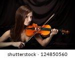 Romantic portrait of beautiful woman with violin, dark background - stock photo