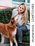 Stock photo beautiful girl with his shetland sheepdog dog sitting and posing in front of camera on wooden bench 1248721483