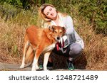 Stock photo pretty girl with his shetland sheepdog dog at nature park outdoor is standing and posing in front 1248721489