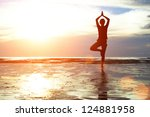 young woman practicing yoga on... | Shutterstock . vector #124881958