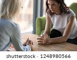 Small photo of Aged and young women sitting staring at each other with distrust and animosity, focus on millennial girl. Different ages various generations employees conflict fight for company position or leadership