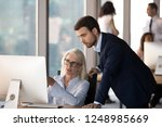 Small photo of Business people using computer, millennial male employee in formal suit helping explaining to middle aged mature female colleague learn understand corporate program. Mentoring and assistance concept