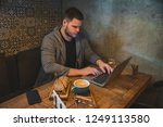 man working on laptop in cafe.... | Shutterstock . vector #1249113580