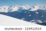 Gondola ski lift and snow covered mountain range in the background. - stock photo