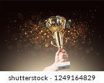 man holding up a gold trophy... | Shutterstock . vector #1249164829