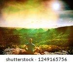 man hiker sitting on a rock in... | Shutterstock . vector #1249165756