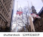 New York, NY / USA- December 3 2018: United States flag and Episcopal flag flying half mast in memoriam for President George H. W. Bush in St. Paul