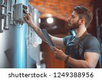 a young handsome brewer in an... | Shutterstock . vector #1249388956