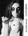Small photo of Horror scene: strange crazy girl with moppet doll and needle in hands. Closeup, black and white