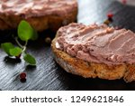 Small photo of Open sandwiches with pate specialty made from pork and turkey liver with sweet cranberry jam on a dark slate